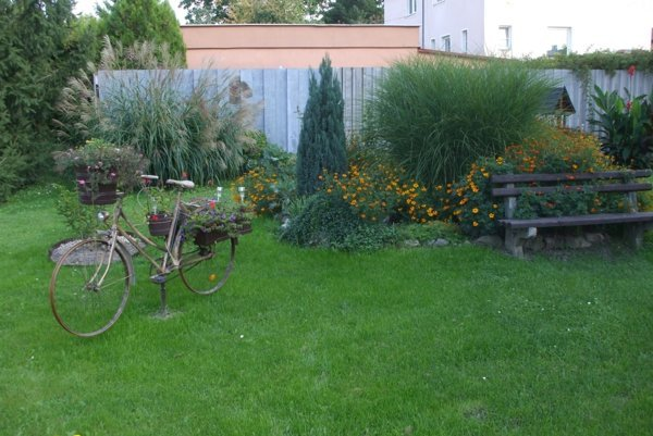 Starý bicykel slúži ako stojan na kvety. Vďaka solárnemu článku večer predné svetlo svieti.