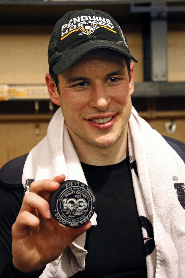 Kanadský hokejista a kapitán Pittsburghu Sidney Crosby pózuje s pukom po tom, čo pokoril hranicu 1000 bodov v kariére v zápase zámorskej hokejovej NHL Pittsburgh Penguins - Winnipeg Jets