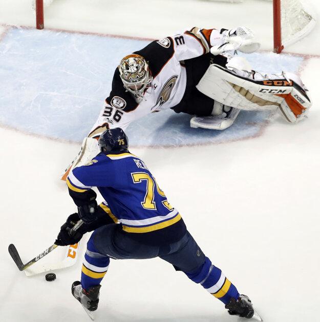 Brankár Anaheimu John Gibson hokejkou vypichuje puk Ryanovi Reavesovi.