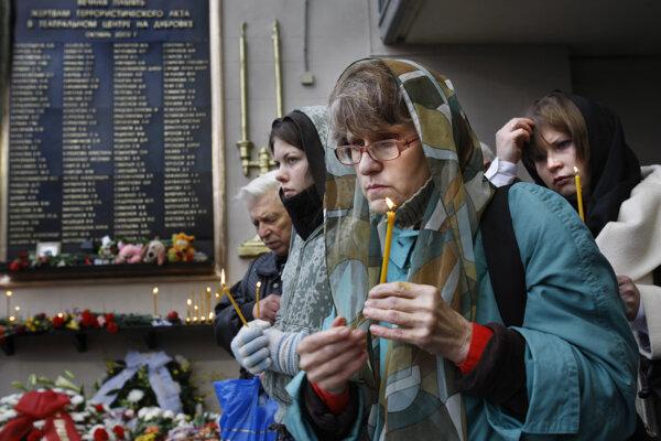 Ľudia pália sviečky pri pamätníku obetí  rukojemníckej drámy v moskovskom divadle Dubrovka.
