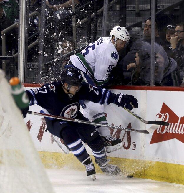 Nikolaj Ehlers z Winnipegu (vľavo) vráža na mantinel hráča Vancouveru Alexa Biegu.