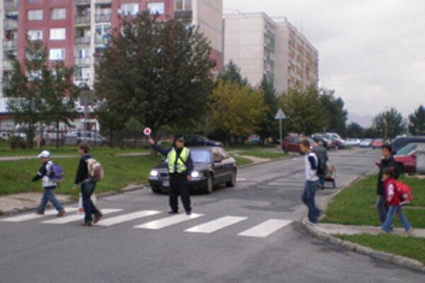 Mestskí policajti usmerňujú dopravu pri školách.