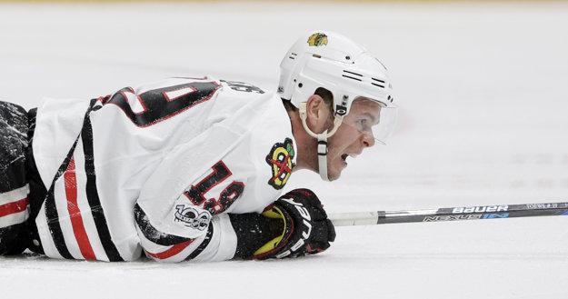 Kapitán Chicaga Jonathan Toews leží na ľade po jednom zo súbojov.
