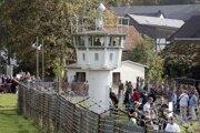 Návštevníci kráčajú okolo kontrolnej veže v obci Mödlareuth, ktorá bola súčasťou bývalého hraničného múru NDR.