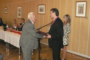 Jozef Bublavý (vľavo) preberá ocenenie za prínos obci Častkovce od syna a starostu Dušana Bublavého.