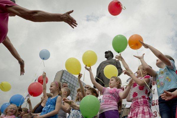 Deti v Donecku vypúšťajú balóny so sochou Lenina v pozadí.