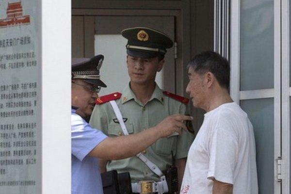 Čínsky policajt sa rozpráva s mužom počas kontroly na Námestí nebeského pokoja.