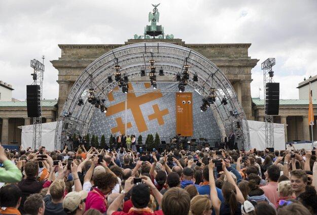 Ľudia sa zhromažďujú pred Brandenburskou bránou, kde na pódiu diskutujú Angela Merkelová a Barack Obama.