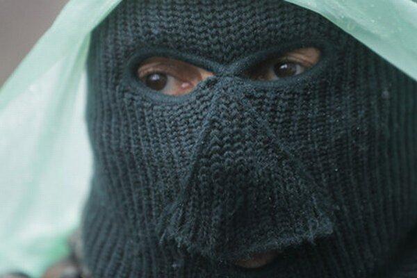 Proruský strelec na stráži pred obsadenou policajnou stanicou vo východoukrajinskom meste Slovjansk.