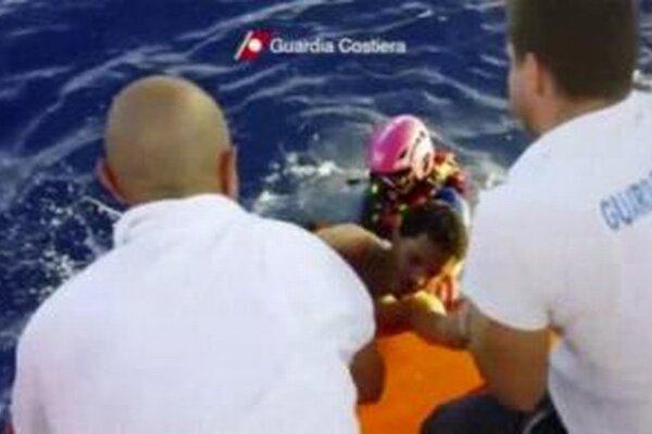 Na videosnímke člen pobrežnej stráže zachraňuje muža, ktorý pochádza z stroskotanej lode.