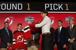 Nico Hischier (v popredí) si oblieka dres New Jersey Devils.