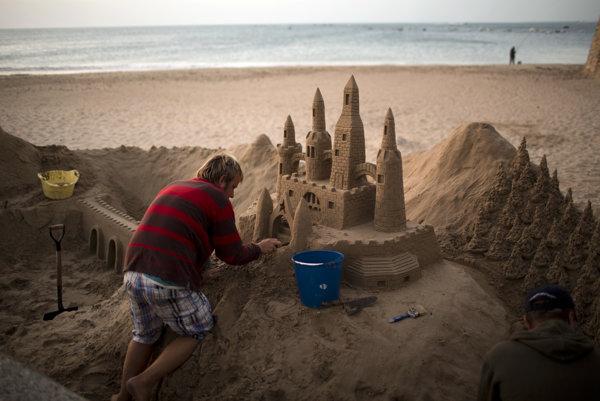 Muž stavia hrad na pláži v španielskom meste Cadiz.