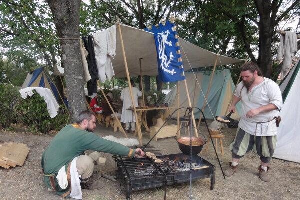 Šermiarsko-divadelná spoločnosť Argyll - v jednom zo stánkov tábora členovia pripravovali jedlo na ohni ak v kotlíku.