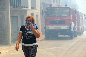 Žena si šatkou zakrýva nos pred dymom z lesného požiaru v mestečku Srinjine v blízkosti Splitu.
