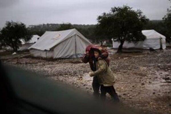 Sýrski chlapci, ktorí opustili svoje domovy s rodičmi, kráčajú v utečeneckom tábore v sýrskom Atmehu.