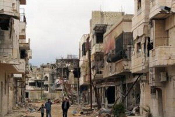 Sýrčania sa prechádzajú medzi zdemolovanými domami v meste Inshaat neďaleko Homsu.