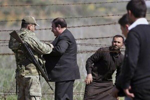 Turecký vojak kontroluje sýrskych utečencov.