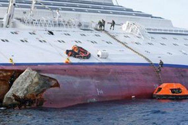 Požiarnici pracujú na boku prevrátenej lode.
