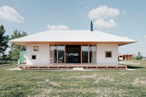 Kategória: Rodinné domy, Dom pri jazere, Vojka nad Dunajom, Jednopodlažnému bungalovu dominuje centrálny obývací priestor s kozubovou pieckou. Sekundárne funkcie sú vytlačené do strán, svojím objemom ohraničujú spoločenskú miestnosť. Harmonikové zasklenie eliminuje rozhranie vnútri – vonku.