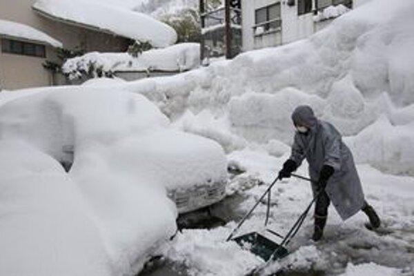 Muž odhŕňa sneh okolo zasypaného auta v Juzawe, severne od Tokia.