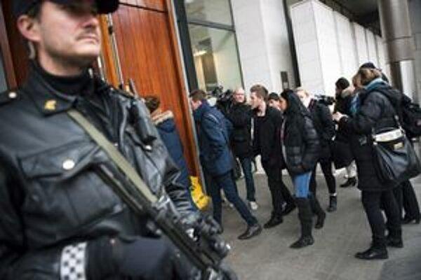 Ozbrojený policajt hliadkuje pred vchodom do budovy súdu.