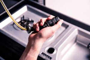 Rozprašovač olivového oleja v tvare páčky pod volantom.