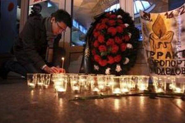 Muž zapaľuje sviečku pri letisku v Moskve.
