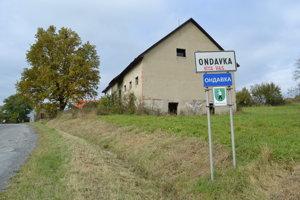 Vstup do obce. Po oboch stranách cesty sú rozpadávajúce sa budovy bývalého družstva.