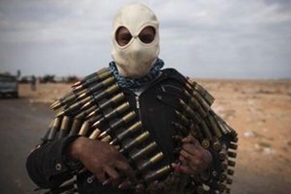 Bojovník protikaddáfíovskej opozície nesie na sebe muníciu na okraji východolíbyjského Rás Lanúf.