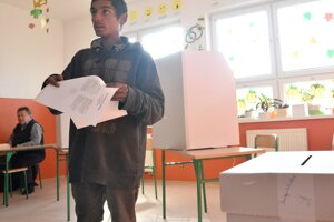 Na snímke volič s hlasovacími lístkami počas volieb do orgánov samosprávnych krajov v rómskej osade v Trebišove.