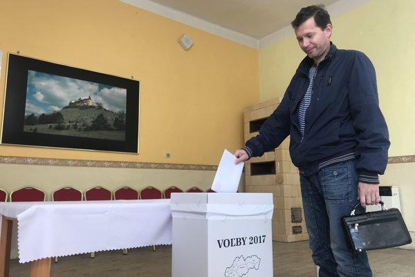 Na snímke volič vhadzuje obálku s hlasovacími lístkami do volebnej schránky počas volieb do orgánov samosprávnych krajov v obci Krásnohorské Podhradie.