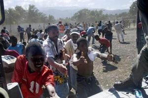 Haiťania utekajú k americkej helikoptére, ktorá priviezla zásoby vody.