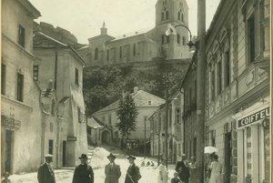 Pohľad na Farskú ulicu v Trenčíne počas jej úprav v rokoch 1927 – 1928. Na fotografii je v kňazskom odeve zachytený trenčiansky starosta Rudolf Misz a pracovníci mestského úradu zodpovední za úpravy – A. Maráky a E. Blažek. V zadnej časti fotografie sa nachádza reklamný pútač propagujúci fotoateliér samotnej fotografky Márie Holoubkovej – Urbasiówny.