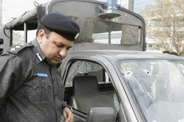 Pakistanský dôstojník kontroluje dostrieľanú policajnú dodávku na mieste útoku.
