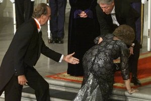 Prezident USA Bill Clinton sa snaží pomôcť španielskej kráľovnej Sofii, ktorá sa potkla na schodoch cestou na obed s kráľom Juanom Carlosom I. (vľavo) a prvou dámou Hillary Rodhamovou Clintonovou v Bielom dome vo februári 2000.