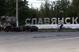 Cyklista prechádza okolo nápisu mesta Slovjansk a vraku kamióna na ceste, ktorá vedie do toho východoukrajinského mesta.
