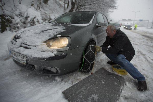Vodič nasadzuje snežné reťaze pred horským priechodom Donovaly.