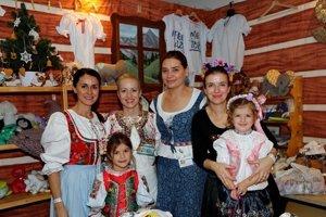 Michaela Brunnerová (vpravo s venčekom) so svojim tímom a deťmi v slovenskom stánku.