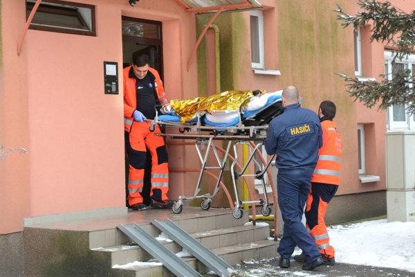 Ženu vyniesli do sanitky na nosidlách.