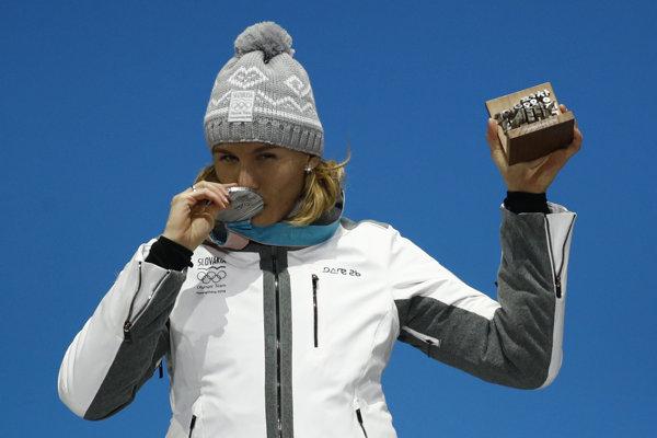 Anastasia Kuzminová bozkáva striebornú medailu, ktorú získala vo vytrvalostných pretekoch na 15 kilometrov.