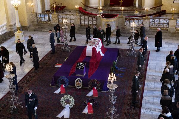 Rakva zahalená dánskou vlajkou a vyzdobená Henrikovým osobným erbom je od soboty vystavená na katafalku v kaplnke paláca.