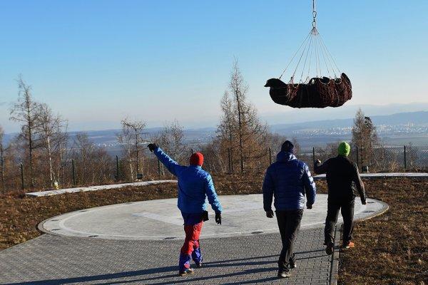 členovia Horskej záchrannej služby prichádzajú odopnúť mŕtve telo horolezca z podvesu vrtuľníka.