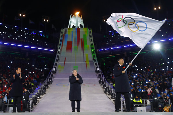Starosta Pekingu máva olympijskou vlajkou.