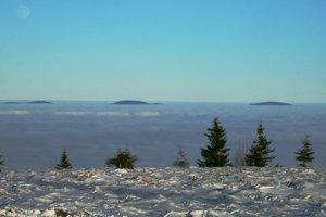 """Výhľad z Kojšovky na východ – z nízkej oblačnosti trčia pod mesiacom len tri """"veľryby"""" Slanských vrchov, tisícovky Šimonka, Čierna hora a Tri chotáre."""