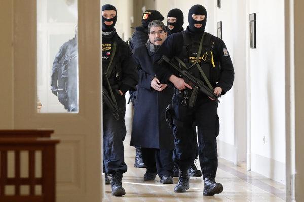 Policajti eskortujú Muslima na súd počas vypočutia v Prahe, marec 2018.