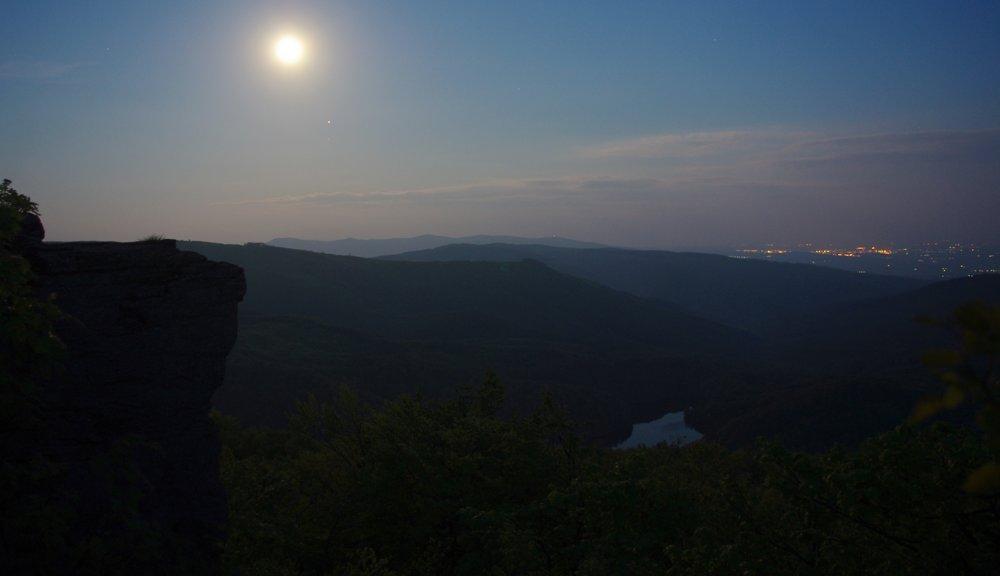 """. """"Nočný kameň"""" – pri splne to môže vyzerať aj ako za bieleho dňa, dole v údolí mesiacom nasvietené Morské oko, na horizonte hrebeň ukrajinsko-slovenskej hranice a vpravo svetla nočných Sobraniec a úplne v pozadí aj Užhorodu."""