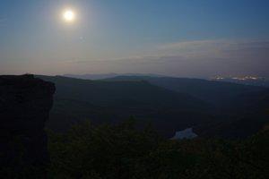 """""""Nočný kameň"""" – pri splne to môže vyzerať aj ako za bieleho dňa, dole v údolí mesiacom nasvietené Morské oko, na horizonte hrebeň ukrajinsko-slovenskej hranice a vpravo svetlá nočných Sobraniec, úplne v pozadí aj Užhorodu."""
