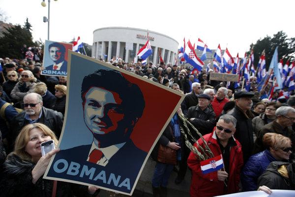 """Žena drží transparent s podobizňou chorvátskejho premiéra Andreja Plenkoviča s nápisom """"Podvod"""" počas protestu proti ratifikácii dohovoru v Záhrebe."""