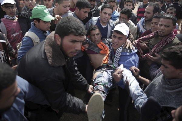 Demonštranti pomáhajú postrelenému Palestíncovi.