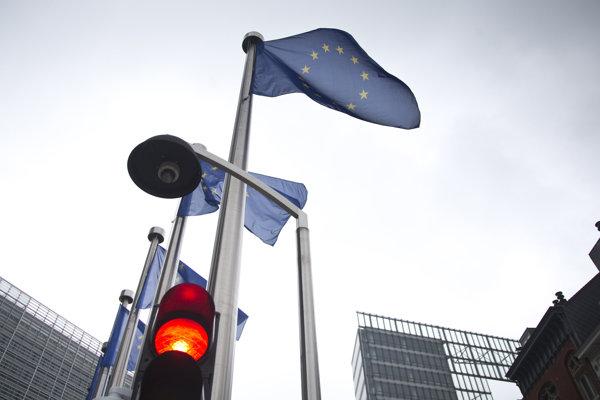 Semafor ukazuje červenú pred vlajkou Európskej únie pred sídlom Európskej únie v Bruseli.